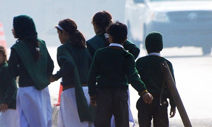Schoolchildren cross a road as they move away from a military run school that is under attack by Taliban gunmen in Peshawar